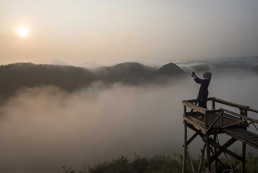 Wisatawan menikmati suasana matahari terbit di Bukit Panguk, Kediwung, Mangunan, Yogyakarta, Senin (11/7). Dataran tinggi yang terletak sekitar 25 Km dari pusat Kota Yogyakarta tersebut menjadi lokasi wisata alternatif untuk menikmati pemandangan matahari terbit.  ANTARA FOTO/Sigid Kurniawan/Spt/16.